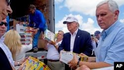 共和党总统候选人川普与竞选伙伴彭斯前往路易斯安那州的洪涝灾区,他们正帮助从卡车上卸下救援物资。(2016年8月19日)