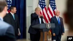 FILE - Presiden Trump Donald Trump, didampingi oleh Wakil Presiden Mike Pence (kanan) dan Sekretaris Negara bagian Kansas Kris Kobach pada 19 Juli, 2017