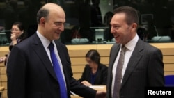 France's Finance Minister Pierre Moscovici talks with Greece's Finance Minister Yannis Stournaras (R) during a Eurogroup meeting in Brussels, December 13, 2012.