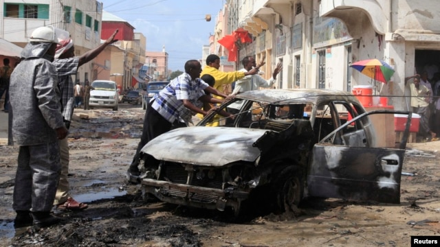 Members of the public and firefighters move the shell of a damaged vehicle after an explosion near the main market in Somalia's capital Mogadishu, July 9, 2013.