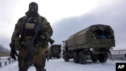 A pro-Russian rebel guards road near Donetsk airport with Ukrainian military vehicles at rear, Eastern Ukraine, Jan. 6, 2015.