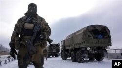 ក្រុមឧទ្ទាមដែលគាំទ្រដោយរុស្ស៊ីយាមល្បាតផ្លូវនៅក្បែរព្រលានយន្តហោះ Donetsk ដែលមានរថយន្តយោធារបស់អ៊ុយក្រែននៅខាងក្រោយ នៅអ៊ុយក្រែនខាងកើត កាលពីថ្ងៃទី៦ ខែមករា ឆ្នាំ២០១៥។