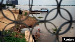 A fisherman casts his net in the Mekong River in Phnom Penh, Cambodia, Nov. 7, 2012.