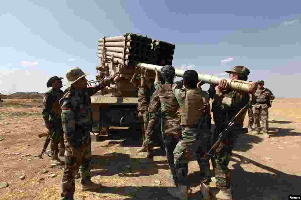 Iraqi Kurdish peshmerga troops load rockets into a launcher during fighting with Islamic State militants in Khazir, Sept. 16, 2014.