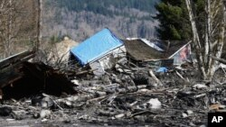 A house is seen destroyed in the mud on Highway 530 next to mile marker 37 in Oso, Washington, March 23, 2014.