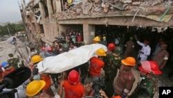 Nhân viên cứu hộ Bangladesh khiêng thi thể của một công nhân xưởng may thiệt mạng ra khỏi tòa nhà bị sụp đổ, ngày 28/4/2013.