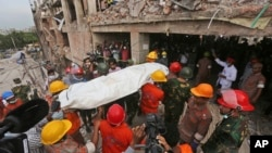 Bangladeshi rescue workers carry the body of a dead garment worker after it was retrieved from a building that collapsed on Wednesday in Savar, near Dhaka, Bangladesh, April 28, 2013.