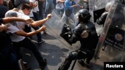 Manifestantes antigubernamentales chocan con la policía durante una protesta en Caracas.