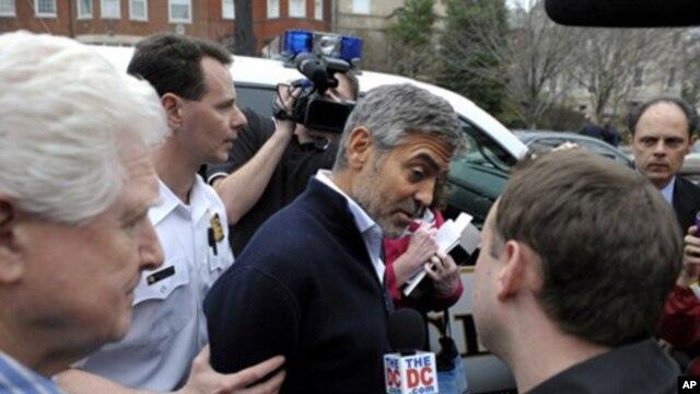 ດາລາຕຸກກະຕາຄຳ George Clooney (ກາງ) ແລະສະມາຊິກສະພາຕໍ່າ ຈາກລັດເວີຈີເນຍ ທ່ານ Jim Moran ຖືກນຳໂຕໄປຂຶ້ນລົດຕຳຫຼວດ ຫຼັງຈາກຖືກຈັບ ໃນການປະທ້ວງຢູ່ນອກສະຖານທູດຊູດານ (16 ມີນາ 2012)