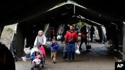Kelompok migran melintasi garis perbatasan antara Serbia dan Kroasia, dekat desa Berkasovo, sekitar 100 kilometer dari Belgrad, Serbia (17/10). Kroasia mengalihkan migran ke Slovenia setelah Hungaria menutup perbatasannya dengan Kroasia.