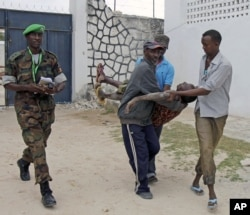 Somali police men in Mogadishu carry a soldier who was injured as two suicide bombers tried to blow up the constituent assembly venue before being shot dead by security forces, Aug.1, 2012.