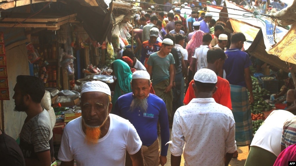 Rohingya refugees walk in market area inside a refugee camp in Ukhia on April 6, 2021 during the second day of weeklong government-imposed lockdown amid an increase of COVID-19 coronavirus cases. (Photo by Miraj KATEB / AFP)