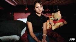 Thiếu nữ ngồi trong một nhà để xe có cửa sổ, nơi cô đã bị giam giữ trong hai năm và phải làm việc 20 tiếng mỗi ngày