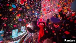 FILE - Revelers toss confetti over Times Square during New Year's Eve celebrations in New York January 1, 2015.