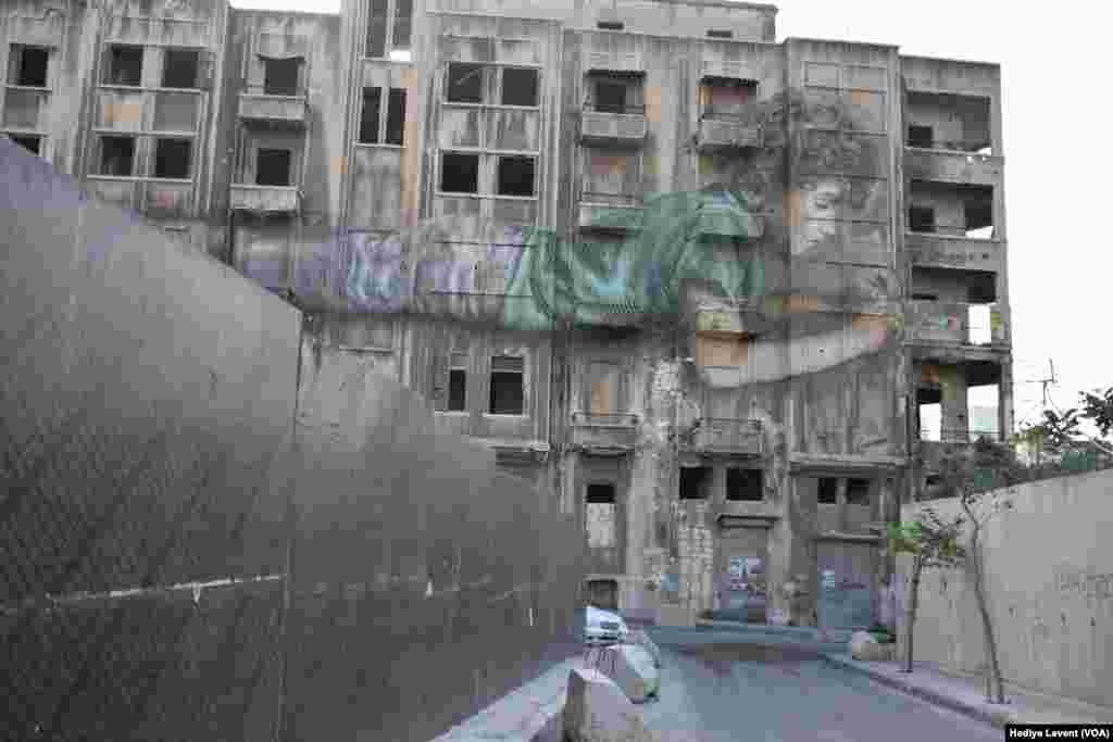 Kendi halinde elektronik devrelerle uğraşan çocuk çok katlı ve çoktan terk edilmiş binanın ön cephesinde duruyor. Bir cepheyi kaplayacak büyüklükteki graffitiler de Beyrut'ta sıkça göze çarpıyor. Bu büyüklükteki ve uğraş gerektiren graffitilerin bazılarının altında yapan sanatçıların isimleri veya en azından imzaları yer alıyor. Ancak yeşil gömlekli ve elektroniğe meraklı çocuğu resmeden sanatçının kim olduğu belirsiz.