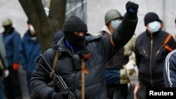 An armed man gestures in front of the police headquarters in Slaviansk, Apr. 12, 2014.
