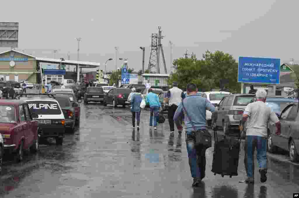People carry their belongings as they walk to cross the border into Russia at the Ukrainian-Russian border checkpoint in Izvaryne, eastern Ukraine, June 20, 2014.