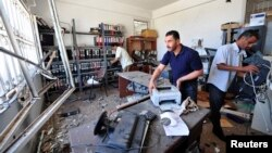 Staff remove damaged items following a bomb explosion at a police station by unknown assailants Benghazi, Libya, May 12, 2013.