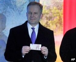 FILE - Governor of Bank of Latvia Ilmars Rimsevics holds a euro note in Riga, Latvia, Feb. 18, 2018.