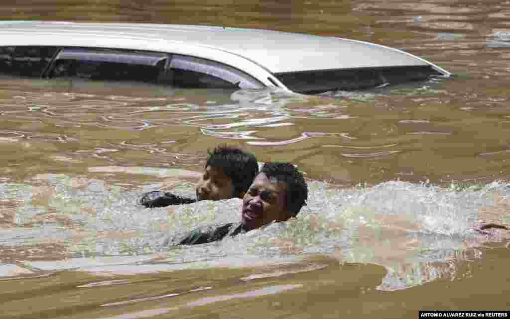 People swim through a flooded neighborhood following heavy rains in Jakarta, Indonesia, Feb. 20, 2021.