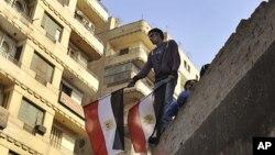 一名年轻人11月26日手持国旗站在开罗解放广场和内政部之间的建筑的屋顶上