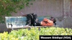 ایک بے گھر شخص ایک بینچ پر سویا ہوا ہے۔