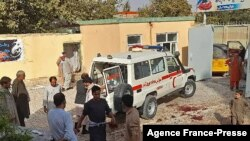 Afghan men stand next to an ambulance after a bomb attack at a mosque in Kunduz on Oct. 8, 2021.