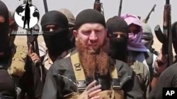 "FILE - Abu Omar al-Shishani, also known as ""Omar the Chechen,"" stands next to Islamic State fighters as they declare elimination of border between Iraq and Syria."