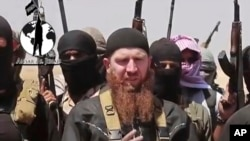 FILE - Omar al-Shishani standing next to Islamic State group spokesman among a group of fighters as they declare elimination of border between Iraq and Syria.