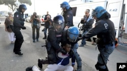 Italian police officers in riot gear remove a migrant in Ventimiglia, at the Italian-French border, June 16, 2015.