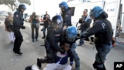 La police italienne saisissant un migrant a Vintimille (Luca Zennaro/ANSA via AP)