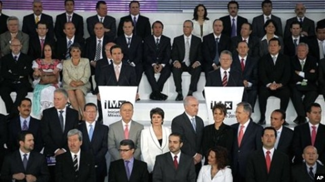 Surrounded by fellow journalists, news media owners, analysts, among others, Carlos Loret de Mola, center left, and Sergio Sarmiento, center right, speak at Mexico Initiative 2011 in Mexico City, March 24, 2011