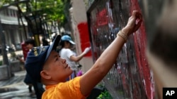 Para demonstran anti-pemerintah membersihkan grafiti dari gerbang utama markas besar Kepolisian Kerajaan Thailand di Bangkok, Thailand (1/3).