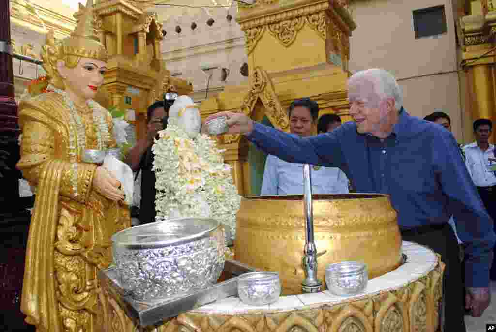 Former U.S. President Jimmy Carter pours water on a Buddha statue as he visits the famed Shwedagon Pagoda Friday, April 5, 2013 in Yangon, Myanmar. Carter arrived in Myanmar Tuesday to support the country's ongoing democratic transition. (AP Photo/Khin Maung Win)