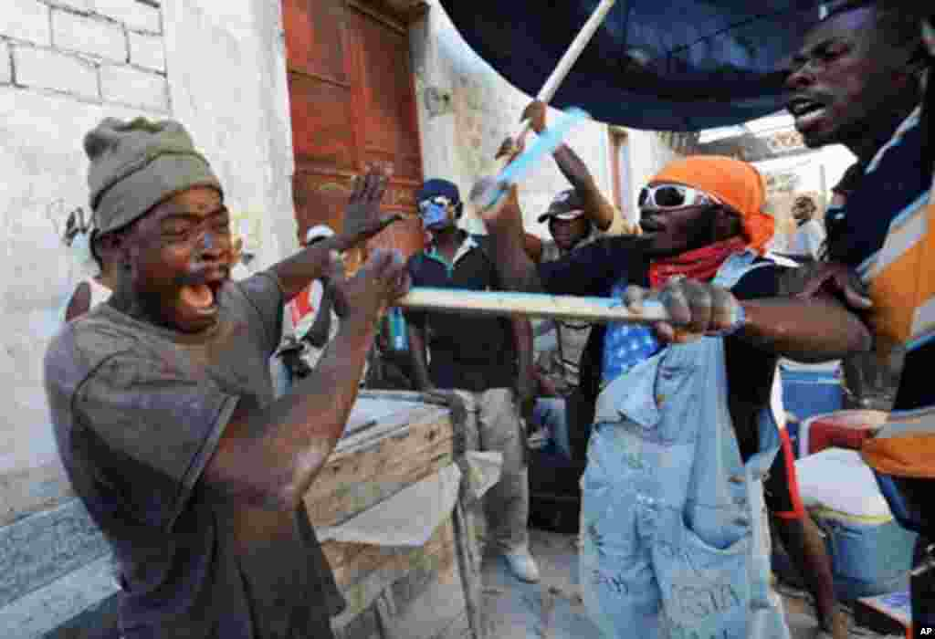 Haitian earthquake victims beat a looter in Port-au-Prince , 21 Jan 2010 - AFP