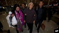 2013年11月6日,盲人法律維權人士陳光誠的母親王金香(中)在另一個兒子陳光福(右)和他們的朋友周莉(左)的攙扶下抵達北京首都機場。王金香與陳光福乘飛機前往紐約和陳光誠團聚。