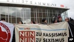 Warga melakukan aksi protes di depan stasiun di Cologne, Jerman, Rabu (6/1).