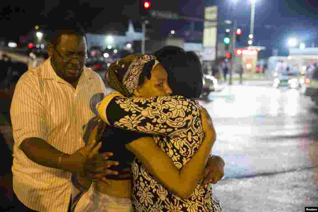 Demonstrators weep on each others shoulders as masked individuals break into a store in Ferguson, Aug. 16, 2014.