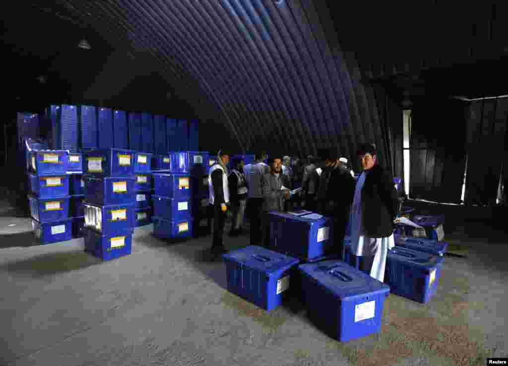 Afghan election commission workers prepare to send ballot boxes and election material to the polling stations at a warehouse in Kabul, April 2, 2014.