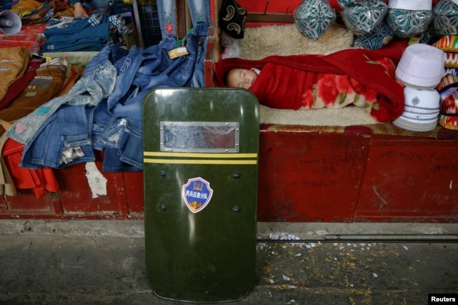 A child sleeps as a riot shield leans on a stall at the bazaar in Hotan, Xinjiang Uighur Autonomous Region, China, March 21, 2017.