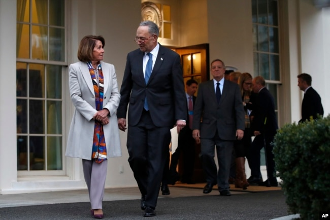 House Democratic leader Nancy Pelosi of California, left, walks with Senate Minority Leader Chuck Schumer, D-N.Y., as Democratic leaders including Sen. Dick Durbin, D-Ill., at right, arrive to speak to the media after meeting with President Donald Trump,