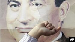 一名埃及女孩在審訊前總統穆巴拉克的法院前的一幅印有埃及前總統穆巴拉克的畫像前高喊。