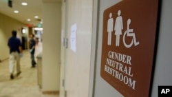 FILE - A sign marks the entrance to a gender-neutral restroom at the University of Vermont in Burlington, Vermont. The Obama administration has issued guidance for transgender students in the United States to be allowed to use the bathrooms that match their gender identity.