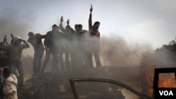 Rebeldes celebran en las afueras de Bengasi tras repeler a las fuerzas de Gadhafi.