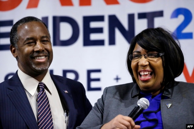 Candy Carson, at right, joins her husband Republican presidential candidate Ben Carson, at left, on stage during a town hall meeting, Feb. 21, 2016, in Reno, Nev.
