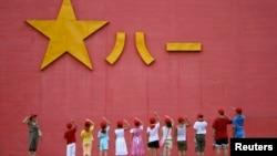 中国小学生向解放军军徽敬礼。(资料照片)