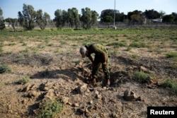 An Israeli soldier inspects a place where a rocket fell near the Israeli kibbutz of Nachal Oz, on the Israeli side of the Israel-Gaza border, July 14, 2018.