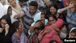 Des membres d'une famille lors des obsèques, lundi, d'une des victimes de l'attentat de Lahore au Pakistan.