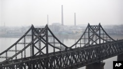 North Korean factories are seen behind a bridge at the waterfront of the Yalu River at the North Korean town of Sinuiju, opposite side of the Chinese border city of Dandong, China, Saturday, March 21, 2009. North Korea detained two Americans for illegally