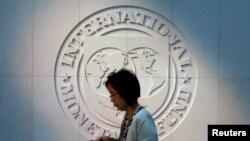 Une femme passe devant le logo du FMI à son siège à Washington, aux États-Unis, le 10 mai 2018. (REUTERS/Yuri Gripas)